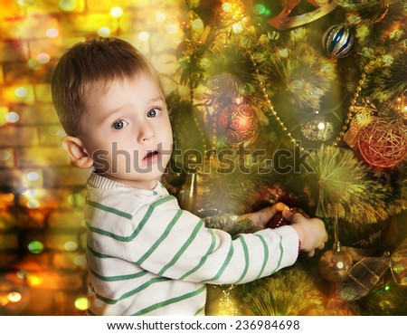 little boy decorates Christmas tree - stock photo