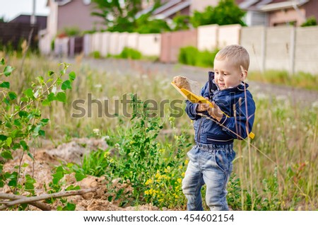 Little boy digs a pit with a shovel in the country