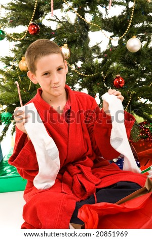 Little boy disappointed to get socks for a Christmas gift. - stock photo