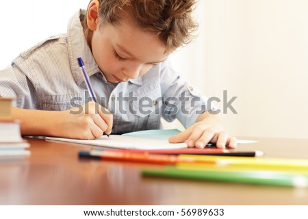 Little boy does a homework - stock photo