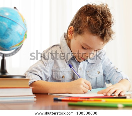 Little boy does house lessons - stock photo