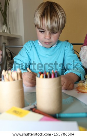 Little boy doing his colouring - stock photo