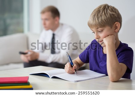Little boy doing his homework alone - stock photo