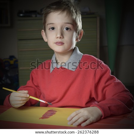 little boy doing homework painting, early education  - stock photo