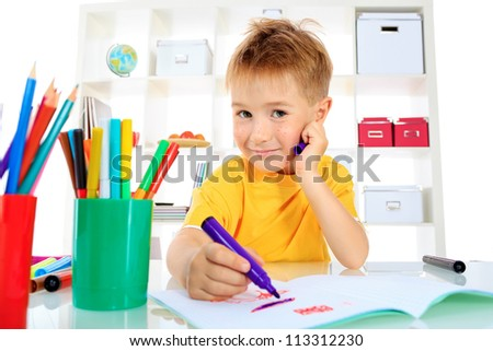 Little boy drawing in his notebook at home. - stock photo