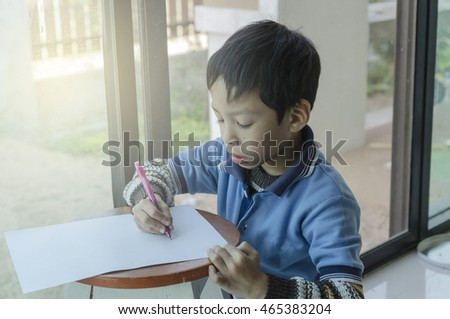 Little boy drawing in paper with lighting sunset from window,Attention Deficit Hyperactivity Disorder,ADHD child acrivity therapy