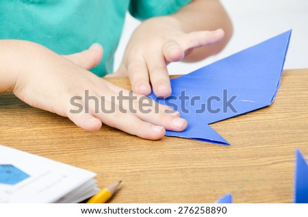 Little boy drawing on paper art origami - stock photo