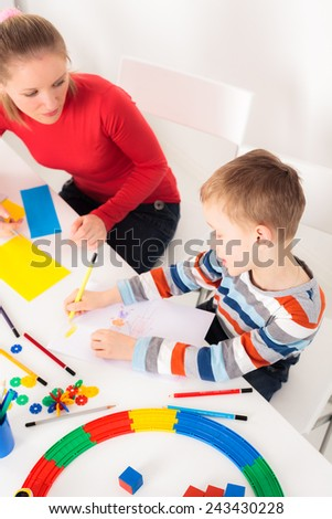 Little boy drawing picture with his mother looking on him