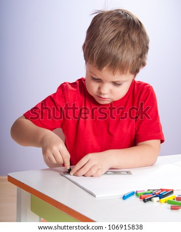 Little boy drawing using crayons