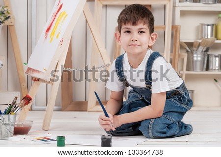 little boy draws in his studio