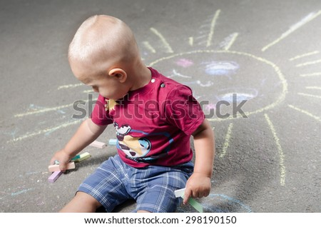 little boy draws with chalk on the pavement sun  - stock photo