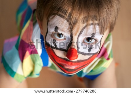 Little boy dressed and painted as clown - with a sad face, looking upwards - stock photo