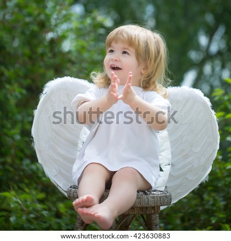 Little boy dressed as angel claps his hands. Happy cupid on the chair