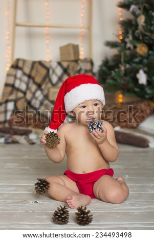 Little boy dressed as Santa sitting in front of a Christmas tree - stock photo
