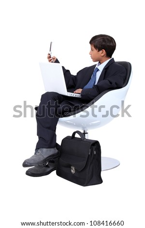 little boy dressed in business man is working - stock photo