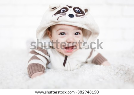 Little boy dressed in raccoon suit and lying on a white soft rug in studio - stock photo