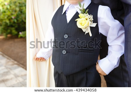 Little boy dressed in suit with boutonniere standing at sunny day outdoor - stock photo