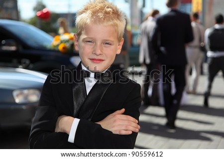 little boy dressed in tuxedo and bow tie standing at sunny day outdoor - stock photo