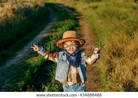 Little boy dressed in Western style in the field - stock photo