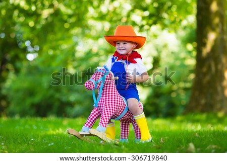 Little boy dressed up as cowboy playing with his toy rocking horse in a summer park. Kids play outdoors. Children in Halloween costumes at trick or treat. Toys for preschooler or toddler child. - stock photo