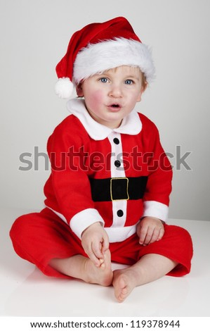 little boy dressed up as Santa Claus for Christmas