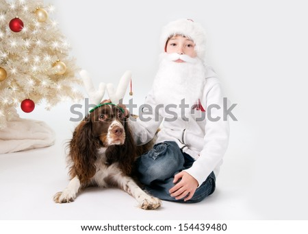 little boy dressed up as santa with his pet dog dressed up as a reindeer