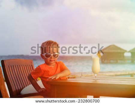little boy drinking cocktail on tropical beach vacation