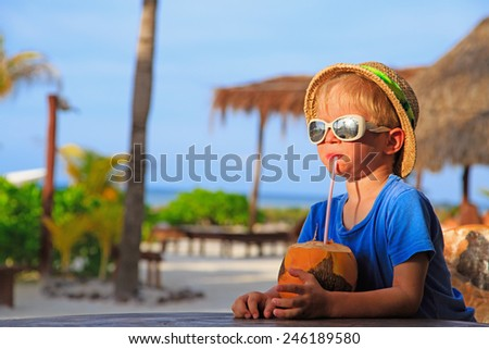 little boy drinking coconut cocktail on tropical beach - stock photo