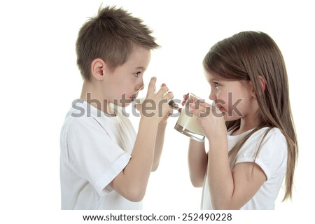Little boy drinking milk on white background. Studio shot