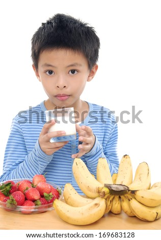 Little boy drinking Milk with banana and apple at the Table - stock photo