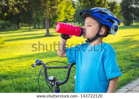 Little boy drinking water by the bike - stock photo