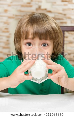 Little boy drinks milk at the table