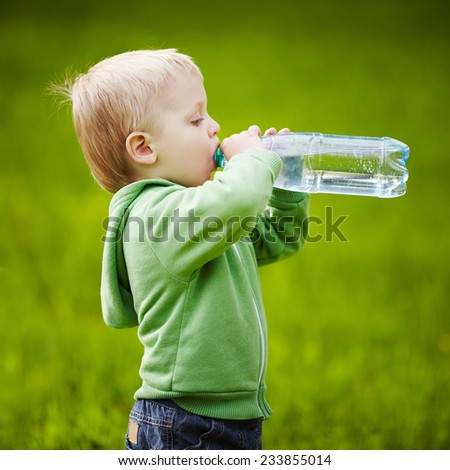 little boy drinks mineral water - stock photo