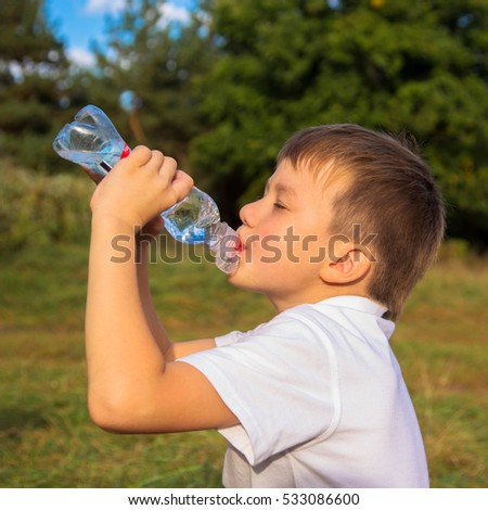 Little boy drinks water from a bottle after running. Healthy lifestyle concept.