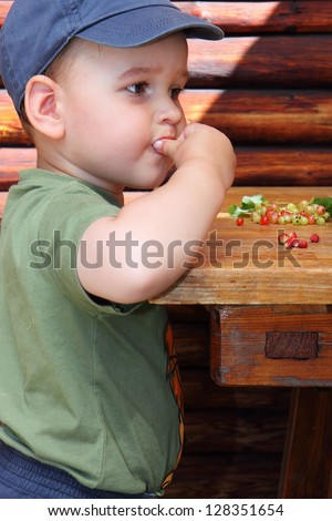 little boy eat forest strawberries and red currants