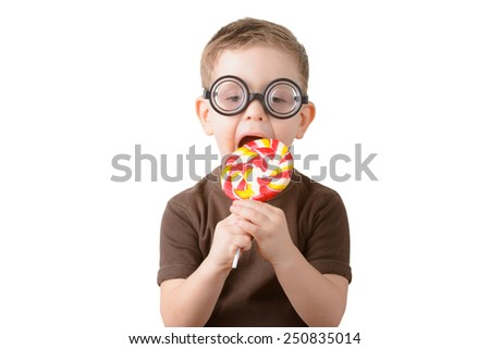 Little boy eating a lollipop with glasses on a white background - stock photo