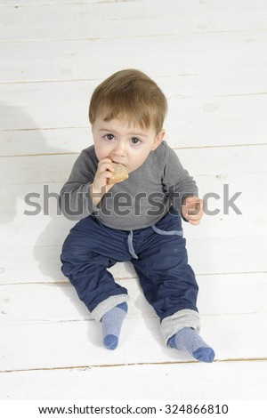 Little boy eating a piece of bread, seated on the floor - stock photo