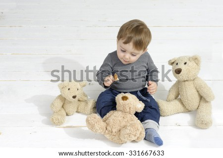 Little boy eating a piece of bread, surrounded by three teddy bears