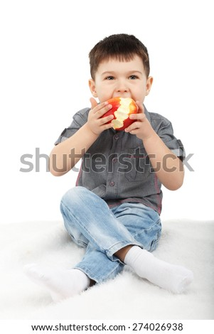 Little boy eating a red apple isolated on white background - stock photo