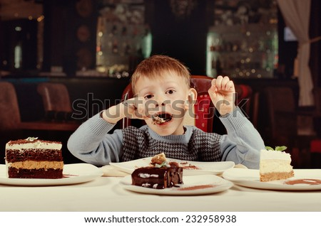Little boy eating a slice of cake with gusto taking a big mouthful as he eyes the line up of different cakes on offer in front of him - stock photo