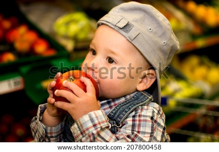 little boy eating an apple in the supermarket - stock photo