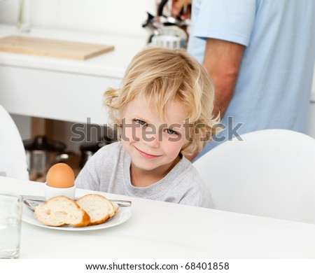 Little boy eating boiled egg and bread at breakfast in the kitchen - stock photo