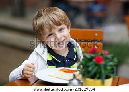Little boy eating cake in outdoor cafe