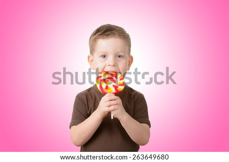 Little boy eating candy on a stick closeup - stock photo