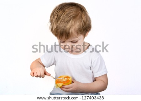 Little boy  eating cheesecake muffin. Isolated on white background.