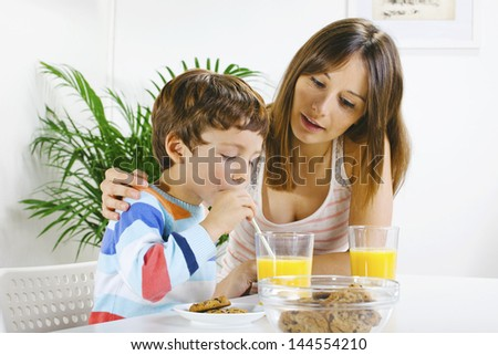 Little boy eating cookies and drinking orange juice with her mum./ Mother and son having breakfast. - stock photo