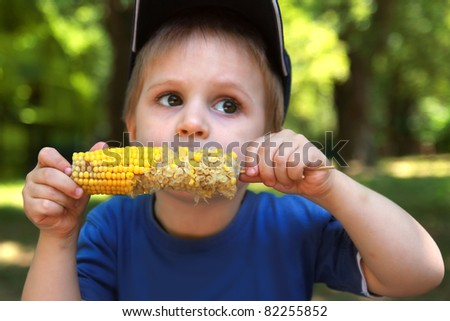 Little boy eating corn on the cob. Focus on the boiled corn - stock photo