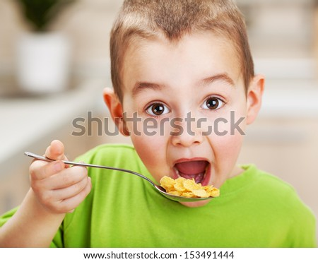 Little boy eating cornflakes for breakfast - stock photo