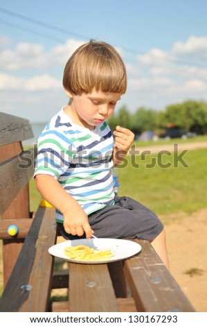 Little boy eating french fries outdoors in a beach resort