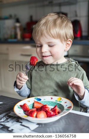 Little boy eating fresh strawberries at home